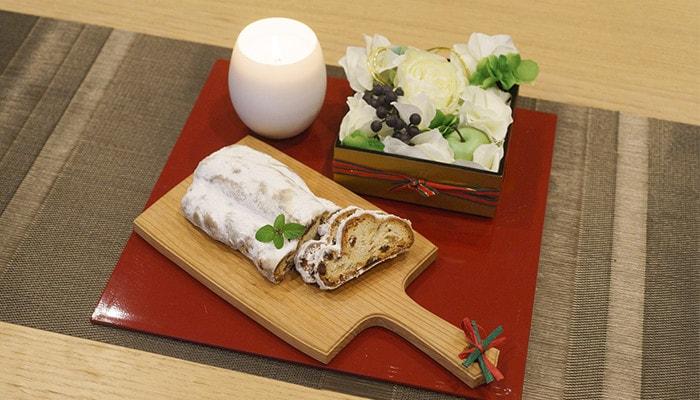 折敷のうえにキャンドルと、パンの乗ったチーズボード、花を敷き詰めたお重が置いてある