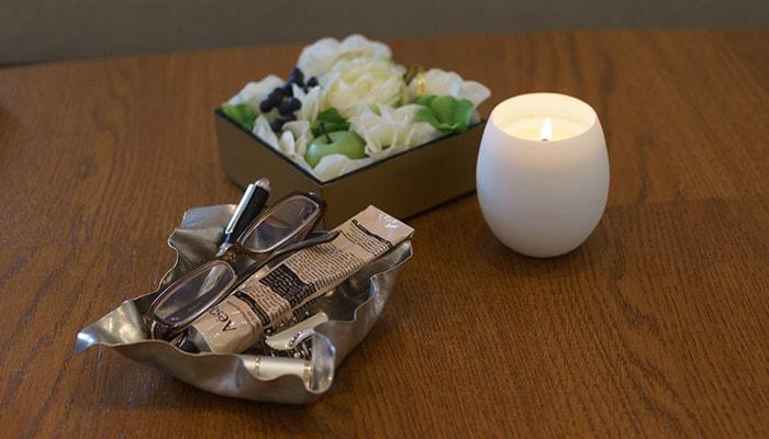 テーブルにキャンドルやすずがみの小物入れ、花の入った重箱が並んでいる