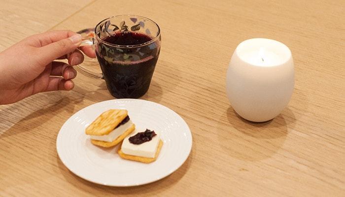 ホットワイン、おつまみ、キャンドルが並んでいて女性がカップを手に取っている様子