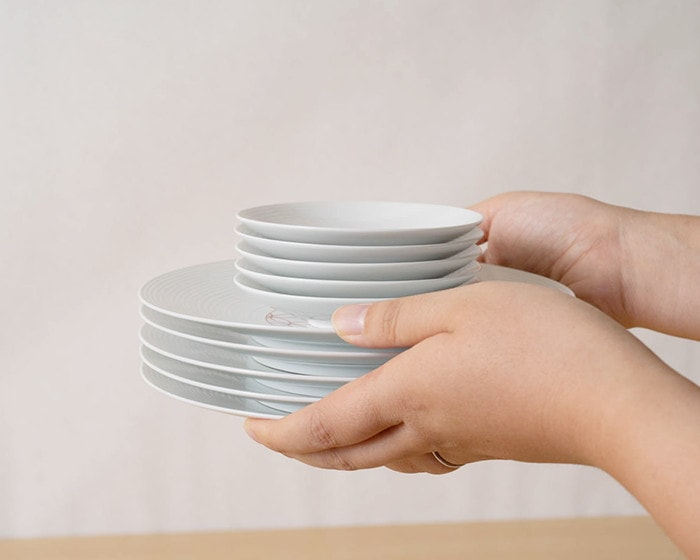 A woman has piles of Japanese dishware of Eiho porcelain