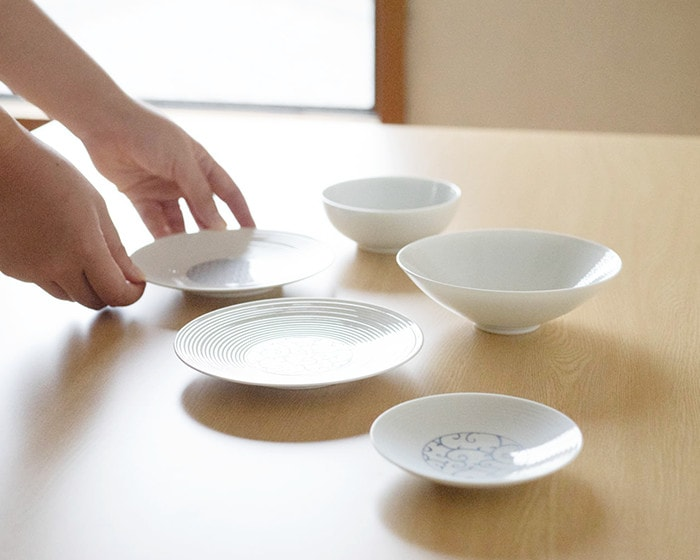 A woman is putting plates of Japanese dishware set