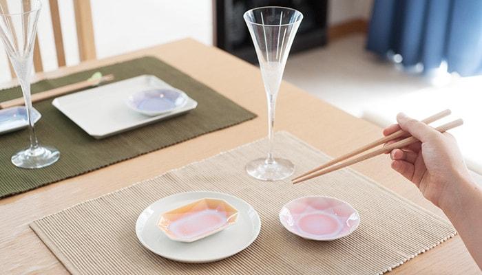 女性が箸を持っていてテーブルには有田ジュエルやシャンパングラスがセットされている