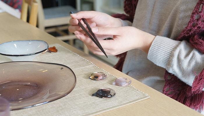 女性が椅子に座って箸を持っていて、テーブルにはfrescoの箸置きやkasumiのプレートが並んでいる