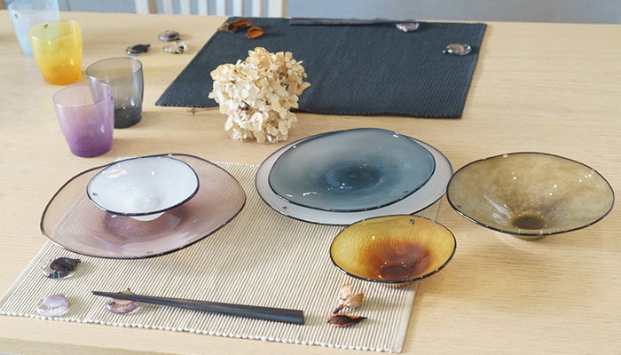 Beautiful table setting with glass plates, bowls, and chopstick rests of fresco