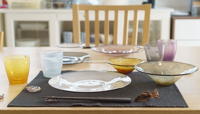 Table setting with glasses, glass plates, and glass bowls of fresco
