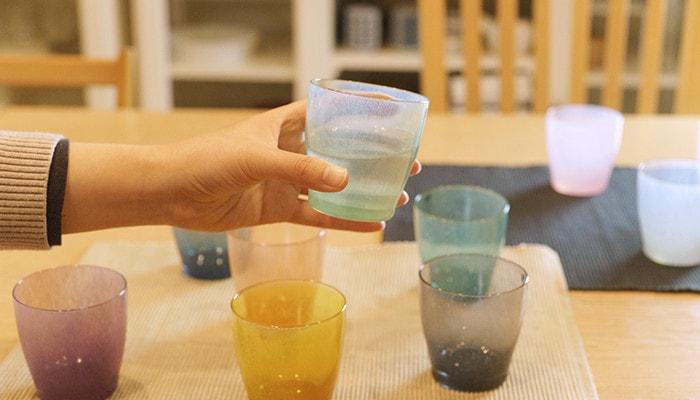 テーブルにいくつかfresco solitoのグラスが並んでいて、内1つのカップを女性が持っている