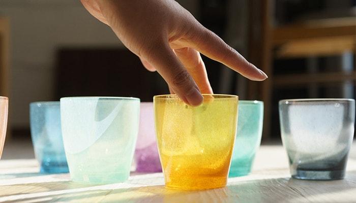 ランダムに並んだfrescoのガラスのコップのひとつに女性が手を添えている