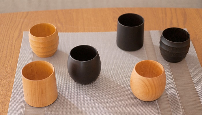 Wooden cups of Gato Mikio on the place mat on the table