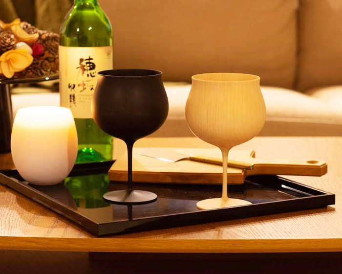 A pair of wooden wine glasses on a tray