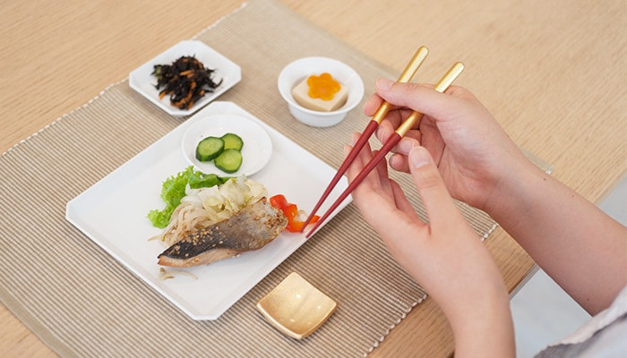 A woman has Shizuku chopsticks and readies to eat lunch