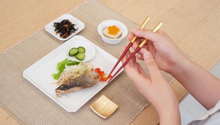 食卓の上に食事が並んでいて女性がしずくの箸を持っている様子