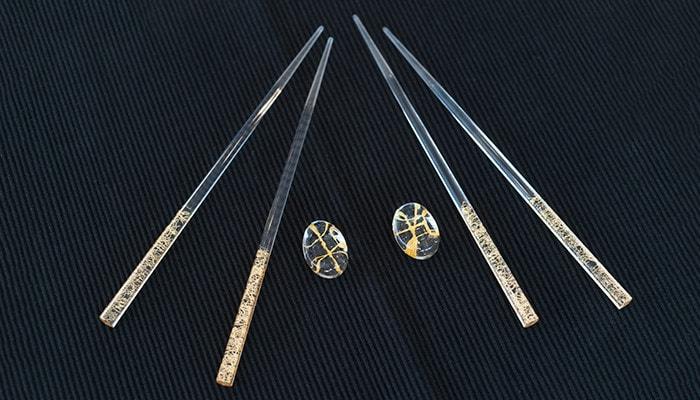 ネイビーのランチョンマットの上にクリア金糸の箸セットが2組置かれている