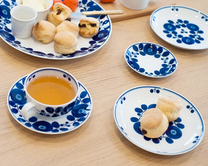 Table setting with piled different sizes of blue and white dishes of Bloom series