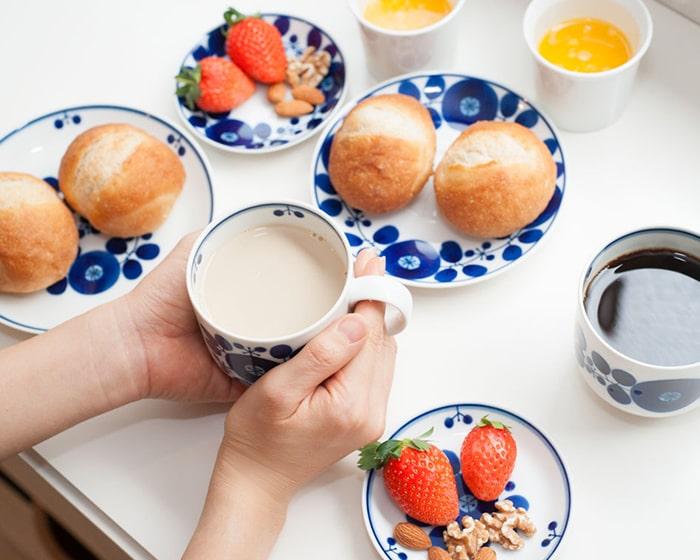 ブルームプレートにはパンやイチゴ、ナッツが盛り付けられていて、女性がカフェオレの入ったブルームマグを手に持っている
