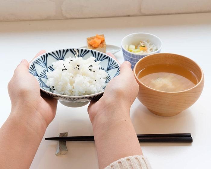 ご飯を盛りつけた平茶碗を両手で持っている様子