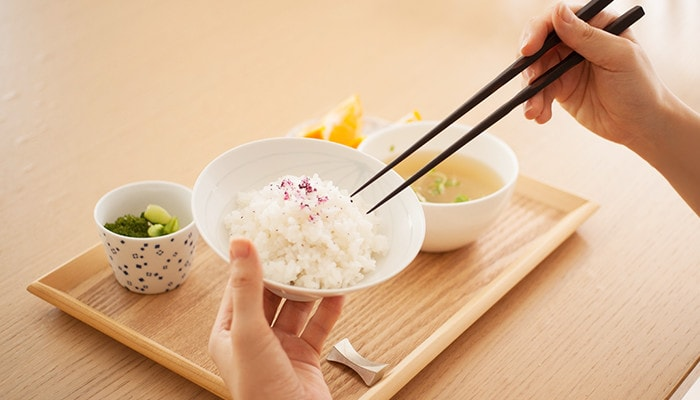 A woman is eating rice on the Japanese bowl of Hakusan Toki