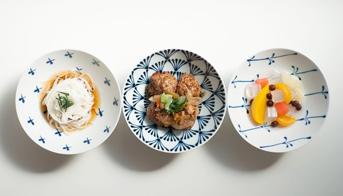 Noodles, meat balls, and fruits on white and navy Japanese bowls