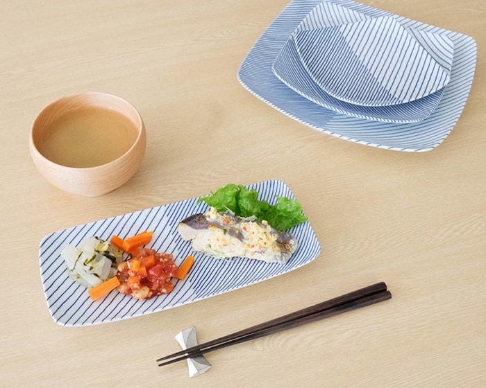 お惣菜が載った重ね縞長皿とスタッキングした重ね縞反角皿