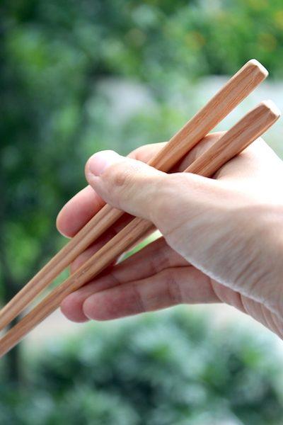 箸蔵まつかんの手作り箸を手に持っている