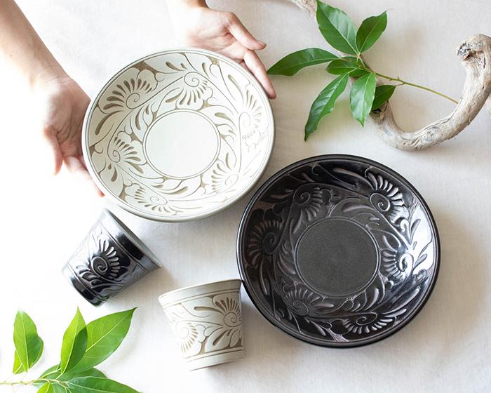 育陶園の唐草シリーズのお皿とフリーカップに手を添えている