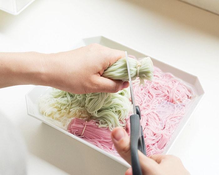 ゆであがった素麺からタコ糸から先の部分をはさみで切っている様子