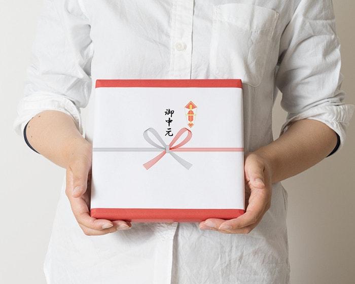女性がお中元の熨斗紙がラッピングされた箱を持っている