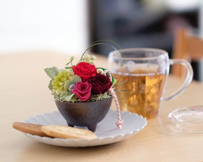 テーブルにプリザーブドフラワーアレンジメントやコーヒーの入ったカップなどが並んでいる