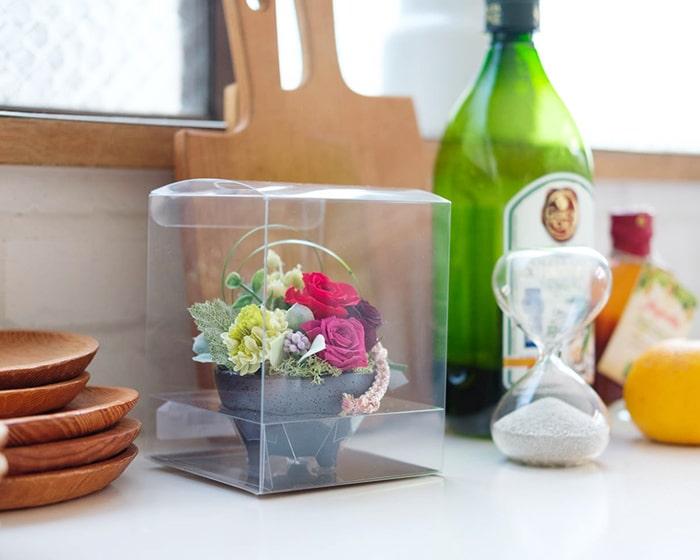 テーブルにプリザーブドフラワーアレンジメントやお花を活けた花瓶、カップなどが並んでいる