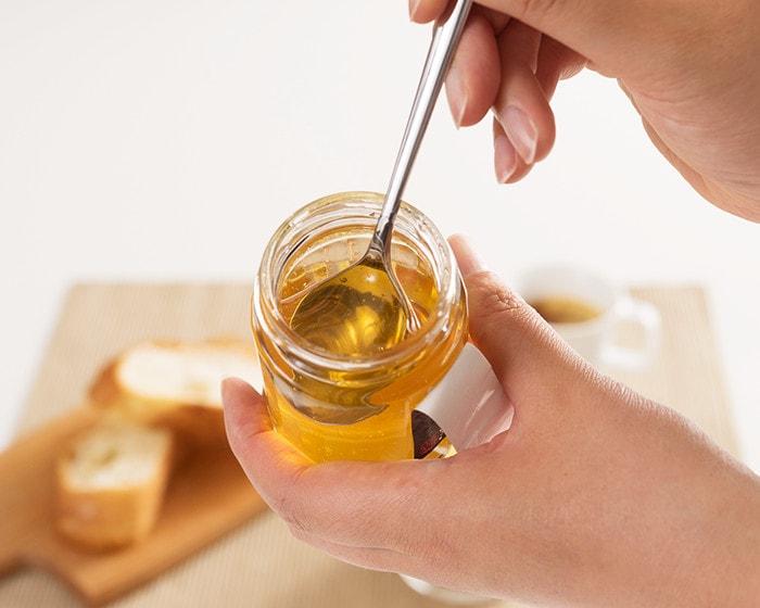 女性が蜂蜜をスプーンで瓶からすくっている様子