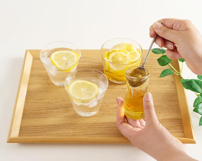 女性がレモンの入った炭酸水にはちみつをかけようとしている様子
