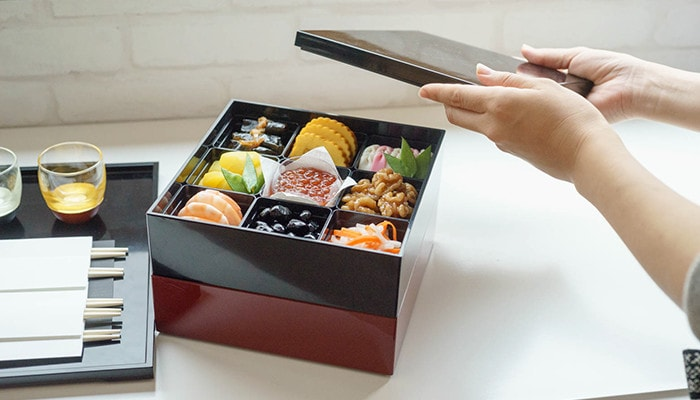 Beautiful Osechi in Jubako box and a woman opens its lid