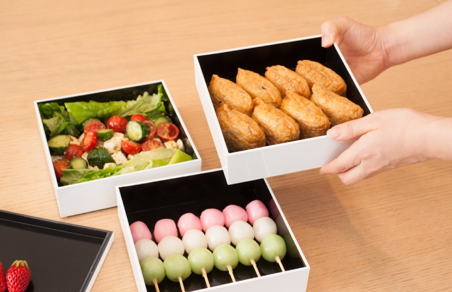 Inari sushi and salad in white Jubako box for picnic