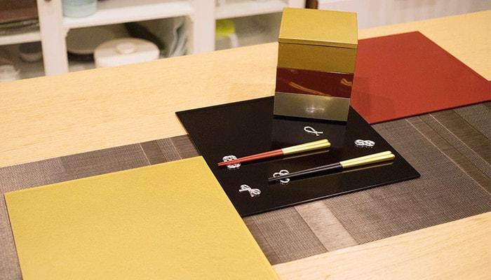 テーブルに折敷や重箱、箸や箸置きが並んでいる