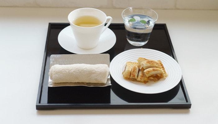 お盆にパイやおしぼり、お茶などが乗っている