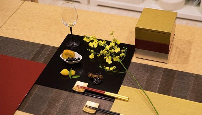 敷膳プレートにお惣菜やワイングラスが乗っている