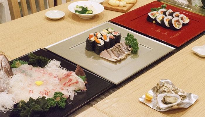 3枚の折敷にそれぞれお寿司やお刺身が盛り付けられている