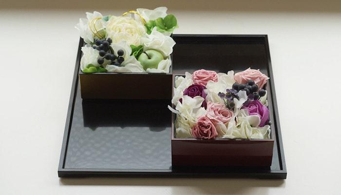 お盆に重箱に入ったお花が2つ飾られている
