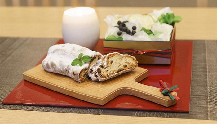 敷膳プレートにパンが乗ったチーズボードやキャンドル、お花の入った重箱が乗っている