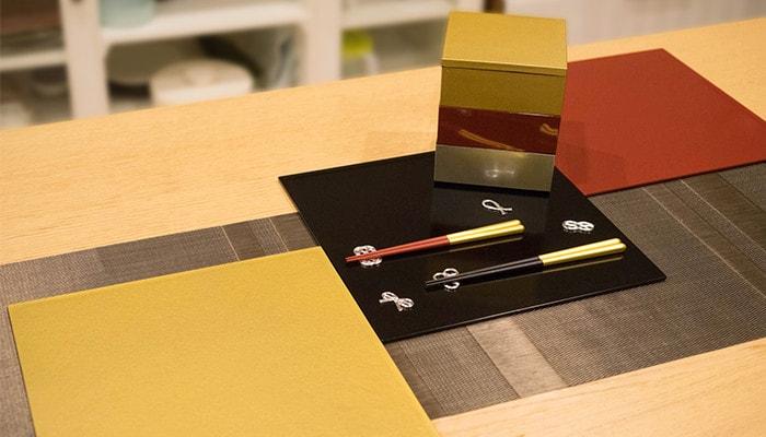 テーブルに折敷や箸セット、重箱が並んでいる