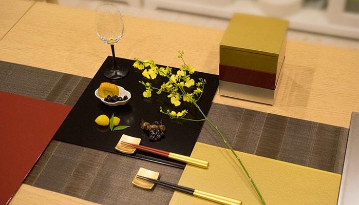 敷膳プレートにお惣菜やワイングラスが乗っている。周りには他の敷膳プレートや箸セット、お花や重箱が並んでいる