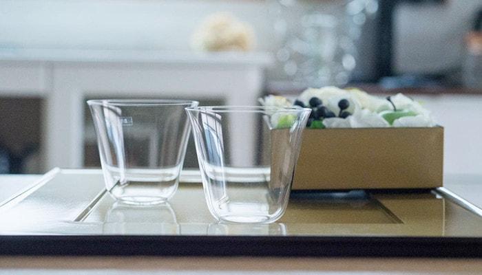 折敷の上に空の薄玻璃(うすはり)グラス・ベッロが2つと花の入った重箱が置いてある