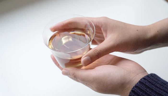 お茶の入った薄玻璃(うすはり)グラス・ベッロを女性が両手でつつむように持っている様子