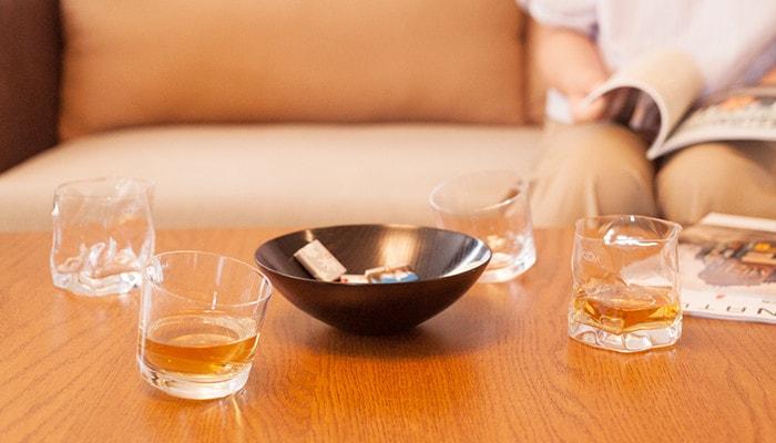 デーブルの上に木村硝子店のロックグラスが4つとお菓子の乗った器が置かれていて奥のソファーには本を読んだ女性が座っている