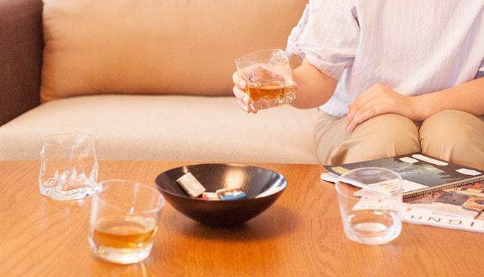 テーブルの上に木村硝子店のロックグラスが3つとお菓子の乗った器が置かれていて奥のソファーに座っている女性がグラスを1つ持っている