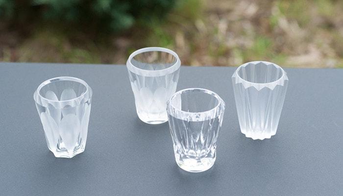グレーの箱の上に木村硝子店のミタテシリーズのグラスが4つランダムに並んでいる