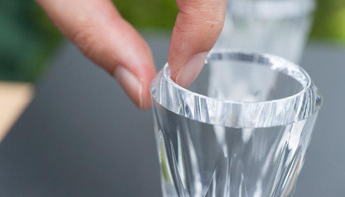 女性が木村硝子店のグラスの口元の厚みを測るように指で挟んでいる