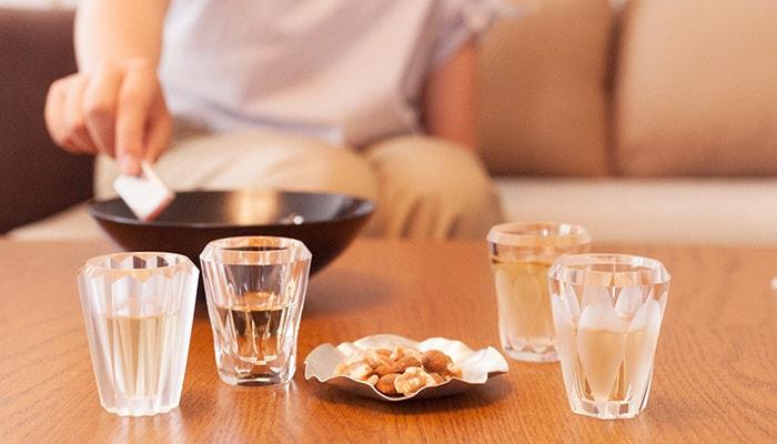 手前のテーブルに飲み物の入った木村硝子店のグラスが4つとナッツのが乗った小皿、奥に女性がソファに座ってお菓子に手を伸ばしている様子