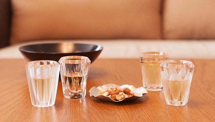 テーブルに飲み物の入った木村硝子店のグラスが4つとナッツのが乗った小皿