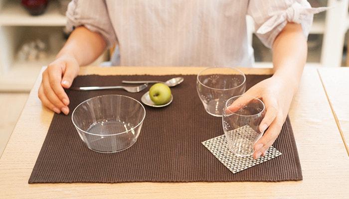 食卓に木村硝子のオーブシリーズの食器が並べられていて、女性がタンブラーを手に持っている様子