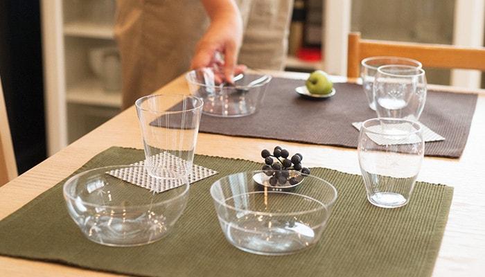 食卓にセットされた木村硝子店の薄玻璃(うすはり)ガラスの食器、奥には食卓をセッティングしている女性の手